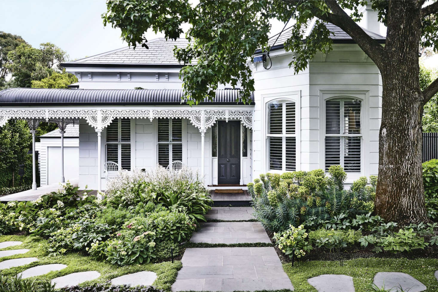 A white Victorian weatherboard facade is offset by a black roof and door. Photograph by Derek Swalwell, courtesy of Ben Scott Garden Design, from Before & After: A Two-Faced Victorian Garden with a Secret.