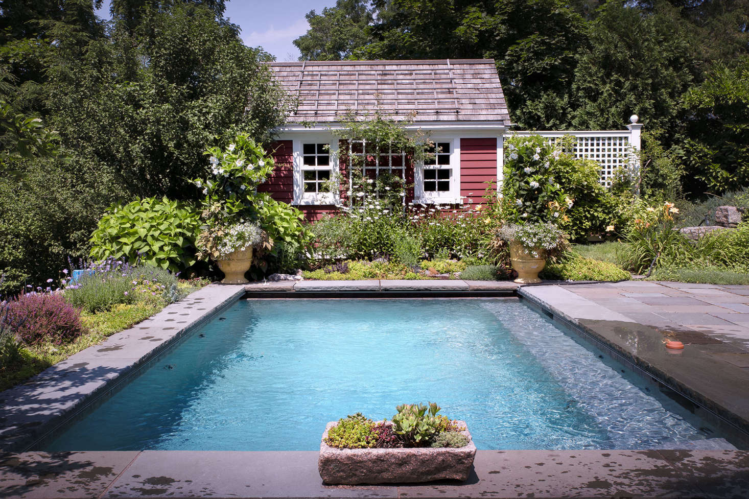 Surrounded by abundant perennials such as Shasta daisies, as well as terra cotta pots planted with vibrant annuals, the rose-covered pool house enhances the cottage feel.