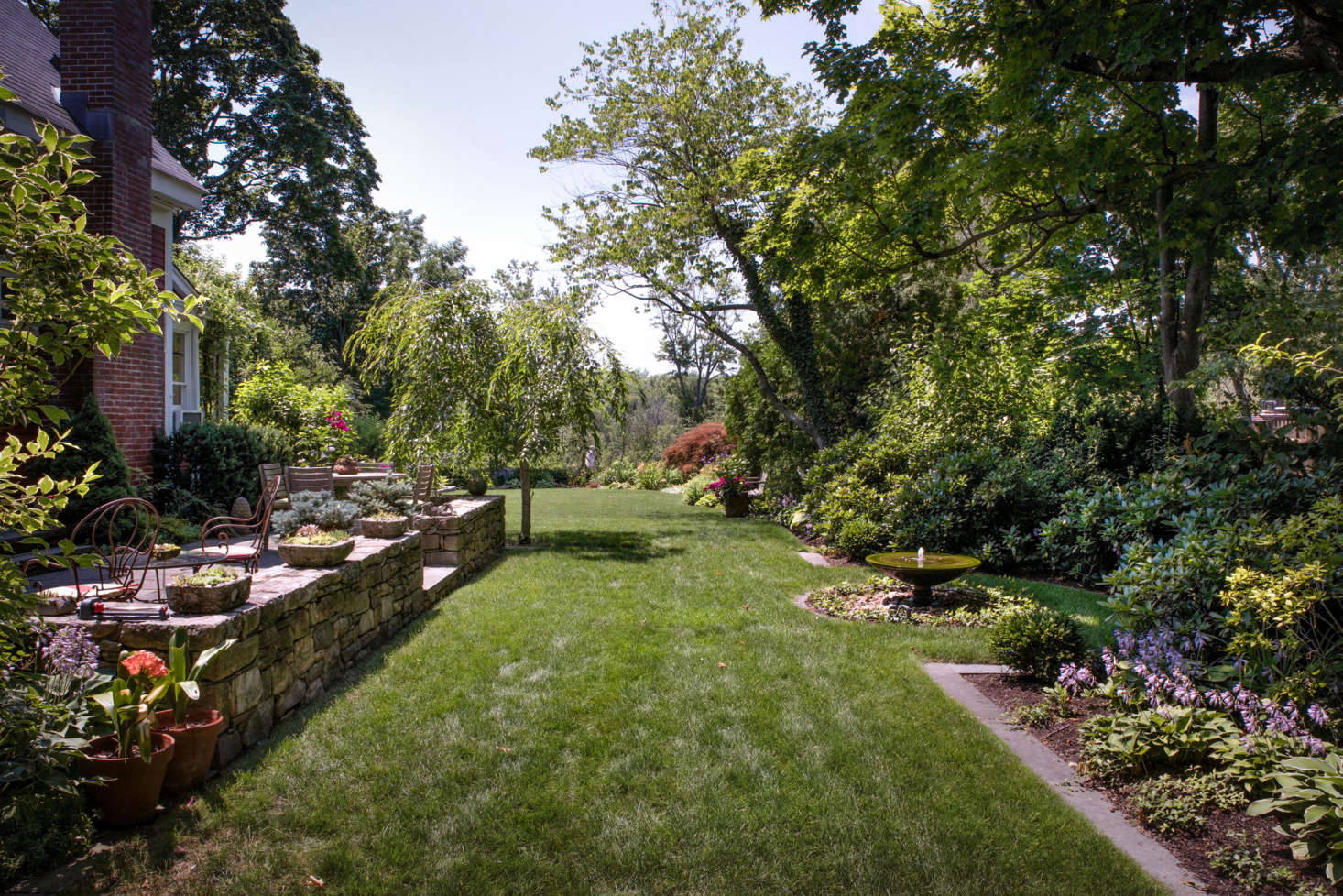 Along the side of the house a stone patio and generous lawn provide a spot for outdoor recreation and entertaining.