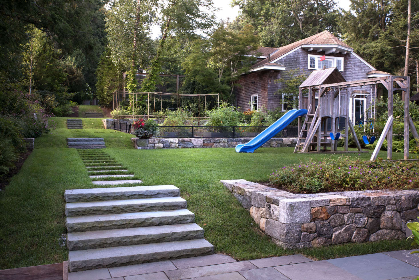 Though it it looks like a single, cohesive space, the backyard actually has a series of five gently graded terraces. At various elevations are a tennis court (behind the garage); an upper garden with a fountain and berry patch; a lower kitchen garden; a play lawn, and (shown in the foreground) a patio next to the house. Newly constructed hardscaping, including low stone walls and bluestone pathways, defines each distinct space and creates visual unity.