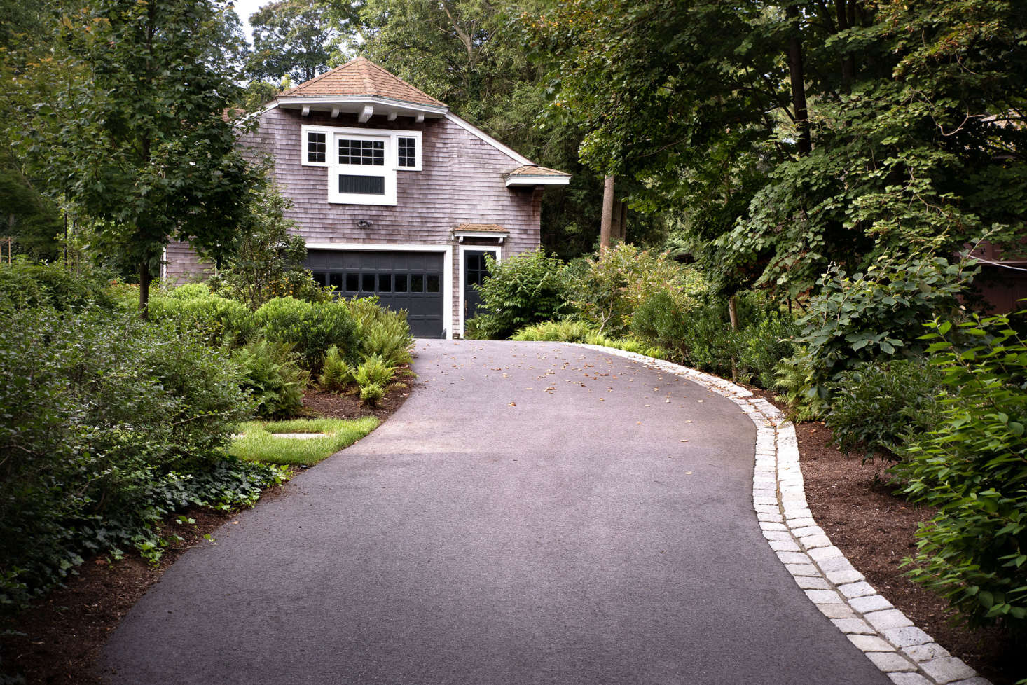 The driveway, which continues past the house to the historic garage, was completely regraded. A new cobblestone edge adds a historically inspired detail, and also channels storm water to prevent the site from flooding.