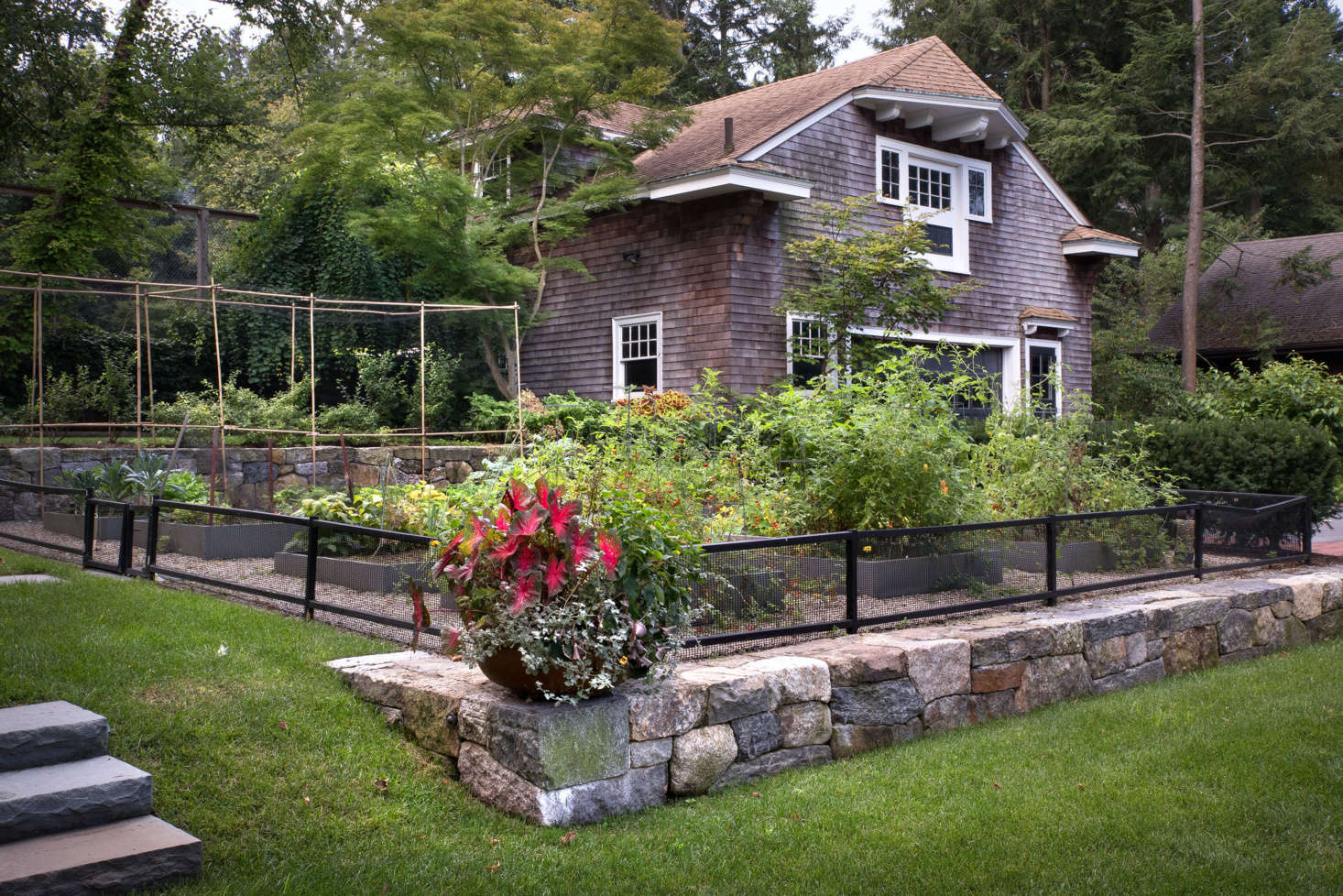 Disappearing into the level above, the stone walls both define and seamlessly blend the distinct parts of the yard.