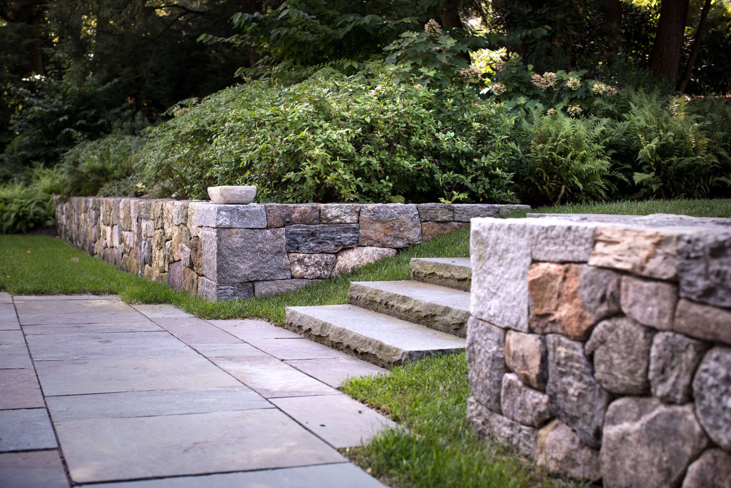 Salvaged granite, puddingstone, and Massachusetts fieldstone were used to in all the retailing walls throughout the property.
