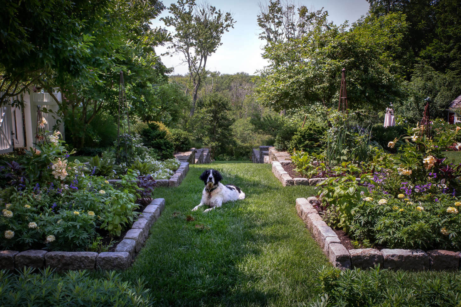 Creating a path that leads past the pool to the lower-level vegetable gardens, four garden beds edged with cobble stones host herbs and flowers.