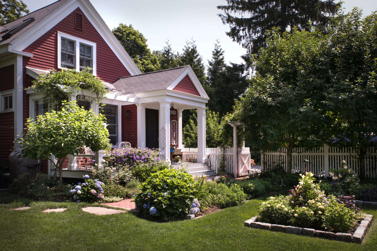 Surrounded by vine-covered pergolas, flowers trees, and perennial borders, the house seems to merge with the garden.