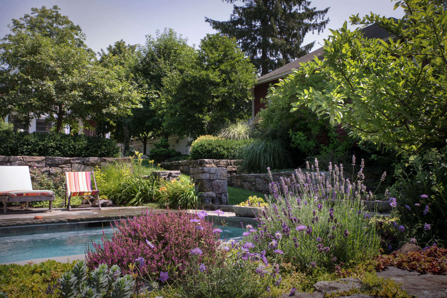Hidden from the main house by a stone retaining wall and lush plantings, the plunge pool feels like a private oasis. A low rock garden on the opposite side provides an unobstructed view of the woods that abut the property.