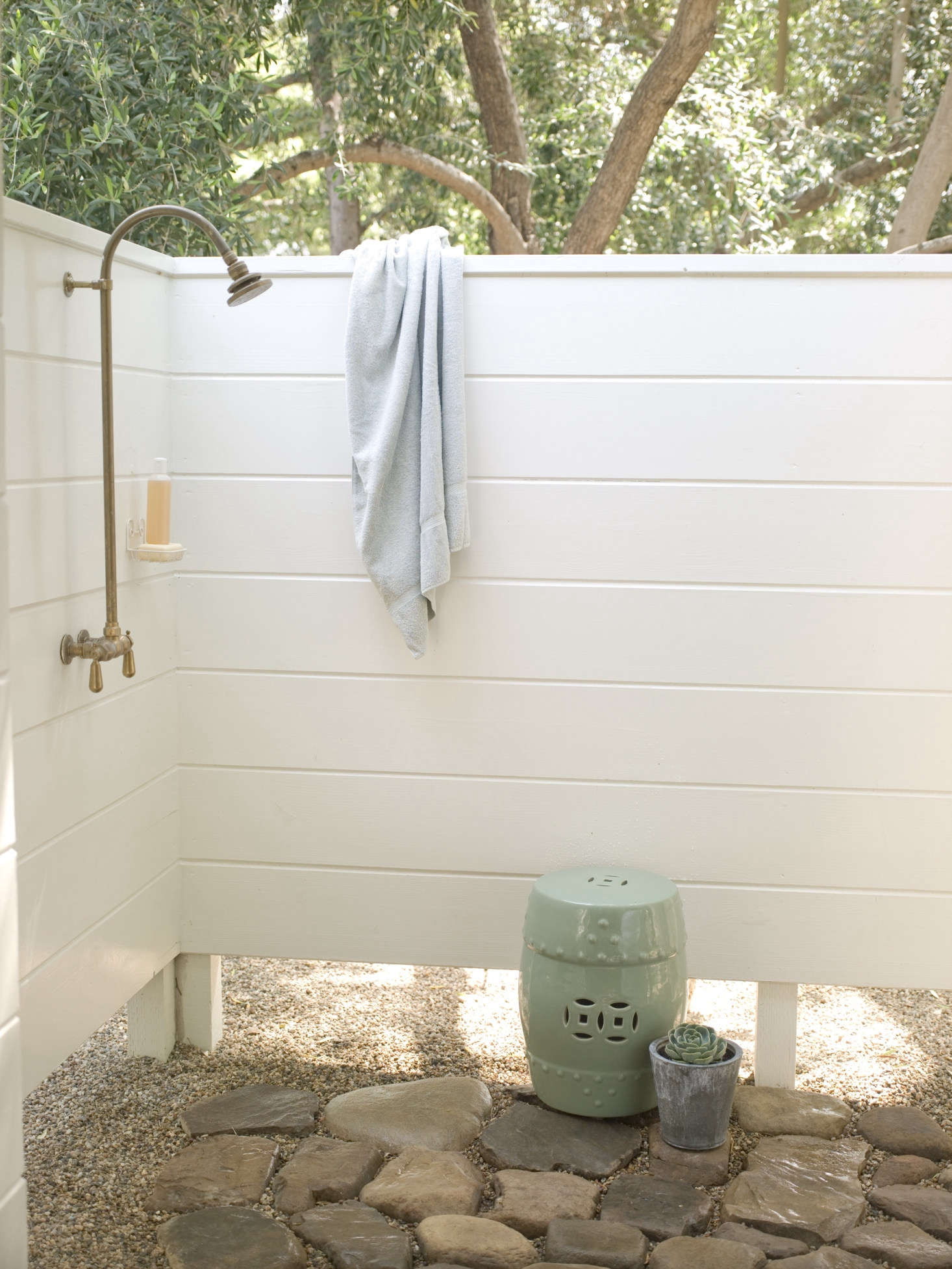 An outdoor shower off of the studio has a stone floor and a privacy enclosure, for rinsing off in the garden.