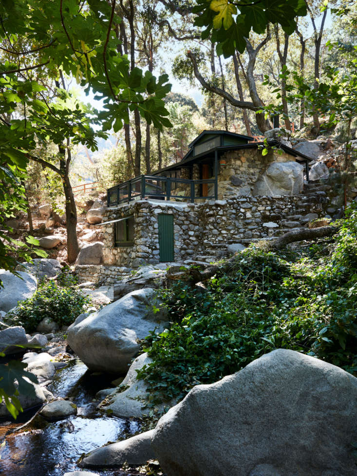 The cabin is perched along a picturesque, boulder-laden stream. The exterior remains unchanged, other than a new front door and fresh paint (Farrow & Ball Studio Green). The lower portion of the cabin is to be a bunkhouse, as yet unfinished.